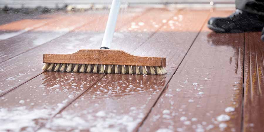 rinsing stripped deck with broom